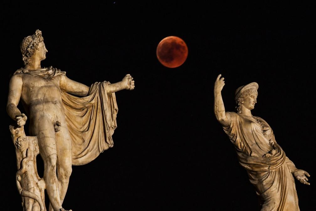 Eclipse da Lua de Sangue visto entre as estátuas de Hera e Apolo em Atenas, na Grécia (Foto: Aris MESSINIS/AFP)