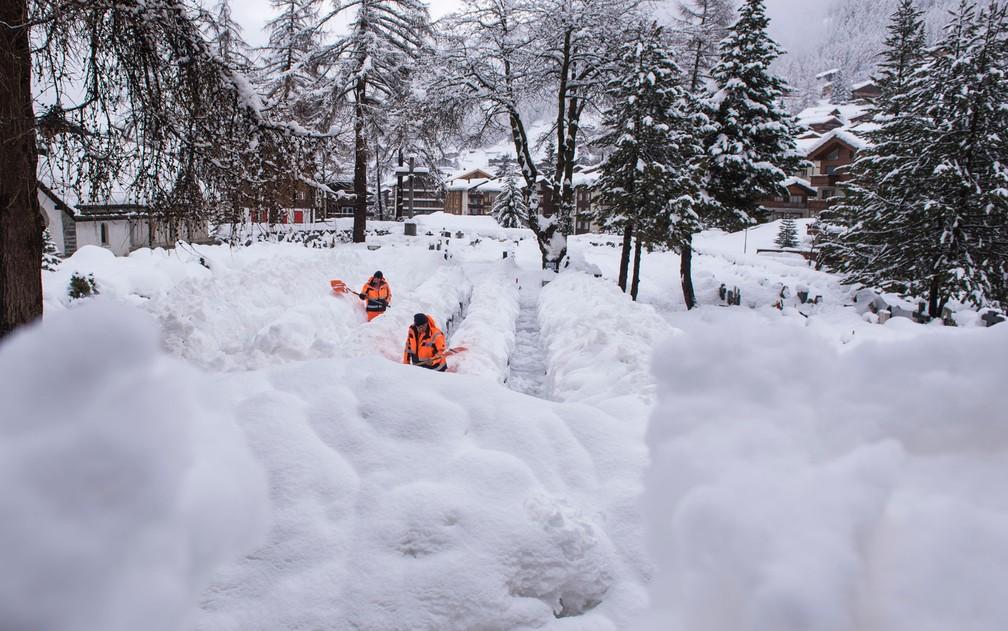 Funcionários abrem caminho na neve em Zermatt, na Suíça, na terça-feira (9) (Foto: Mateusz Bocian/Keystone via AP)