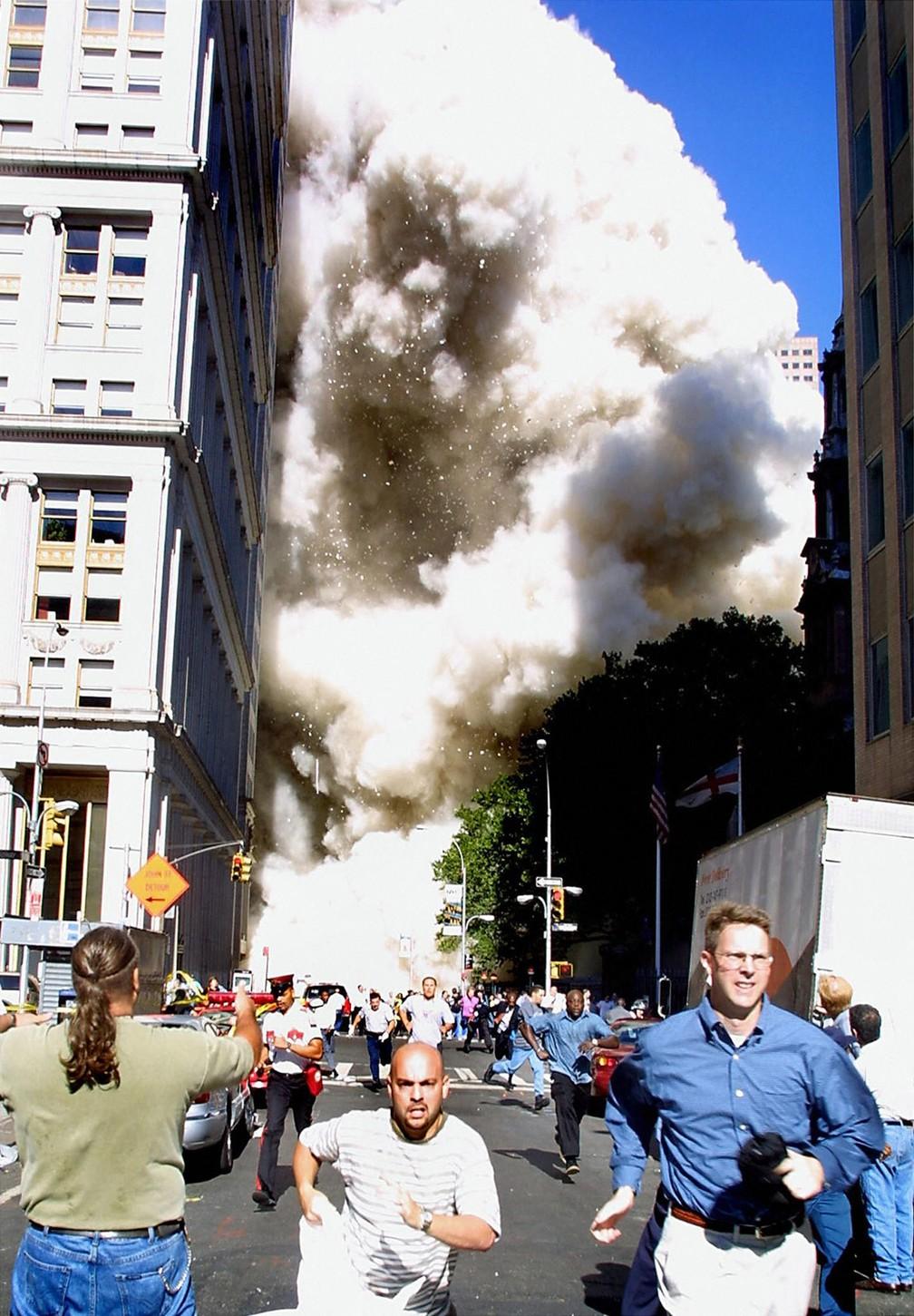 Pedestres correm enquanto uma das torres do World Trade Center vem abaixo e uma nuvem de poeira e destroços se aproxima em Nova York, no dia 11 de setembro de 2001 — Foto: Doug Kanter/AFP/Arquivo