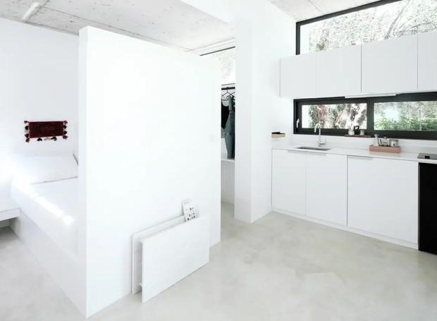 O espaço integrado do interior é composto por cozinha, mesa, quarto e banheiro. Uma parede pequena divide o living e a área para dormir (Foto: Apartment Therapy/ Reprodução)