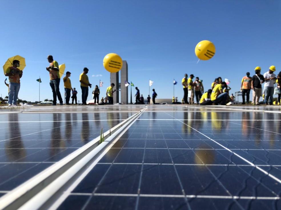 Manifestantes montam painel de energia solar no gramado do Congresso Nacional para pedir pagamento de impostos no setor — Foto: Walder Galvão/G1
