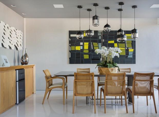 Na sala de jantar, jogo de luminárias e quadro com toques de amarelo, verde e azul levantam o ambiente. Mesa de jantar, cadeiras e pendentes da Finish Móveis.  (Foto: Denilson Machado/Divulgação)