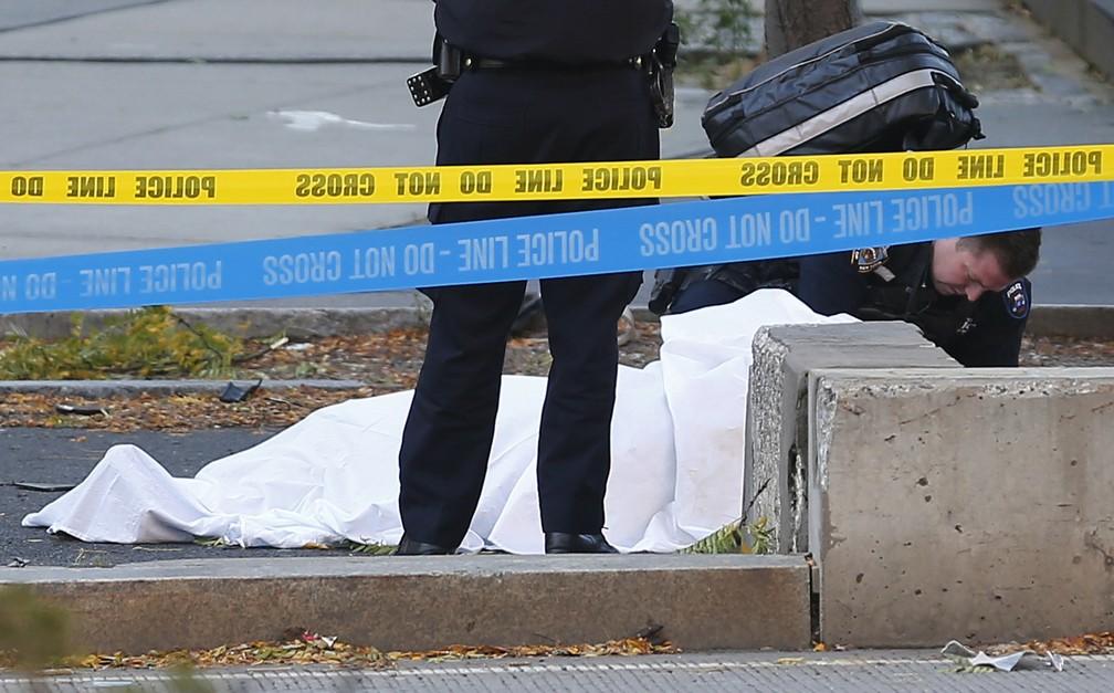 Policial é visto ao lado de corpo coberto perto de uma ciclovia nesta terça-feira (31) em Nova York  (Foto: Bebeto Matthews/AP)