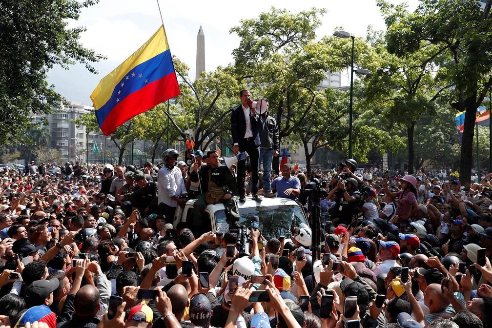 Juan Guaidó fala com megafone a multidão de cima de um carro em Caracas, após convocar o povo às ruas contra Maduro — Foto: Carlos Garcia Rawlins/Reuters