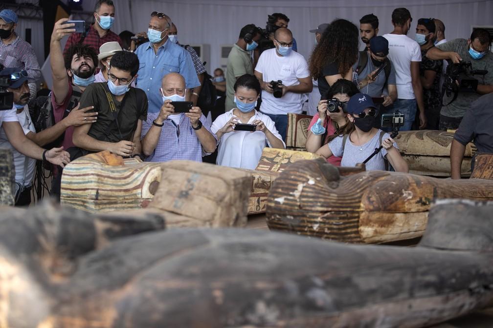 Sarcófagos com cerca de 2,5 mil anos são exibidos no sítio arqueológico de Saqqara, no Egito. O Egito diz que os arqueólogos desenterraram cerca de 60 caixões antigos em uma vasta necrópole ao sul do Cairo. O ministro egípcio de Turismo e Antiguidades disse que pelo menos 59 sarcófagos lacrados com múmias dentro foram encontrados, enterrados em três poços — Foto: Mahmoud Khaled/AP