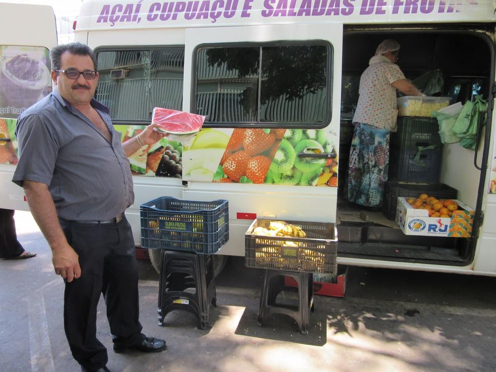 O empresário José Guedes segura fatia de melancia; ele vende até 70 fatias por dia durante a época de calor em Brasília (Foto: Raquel Morais/G1)
