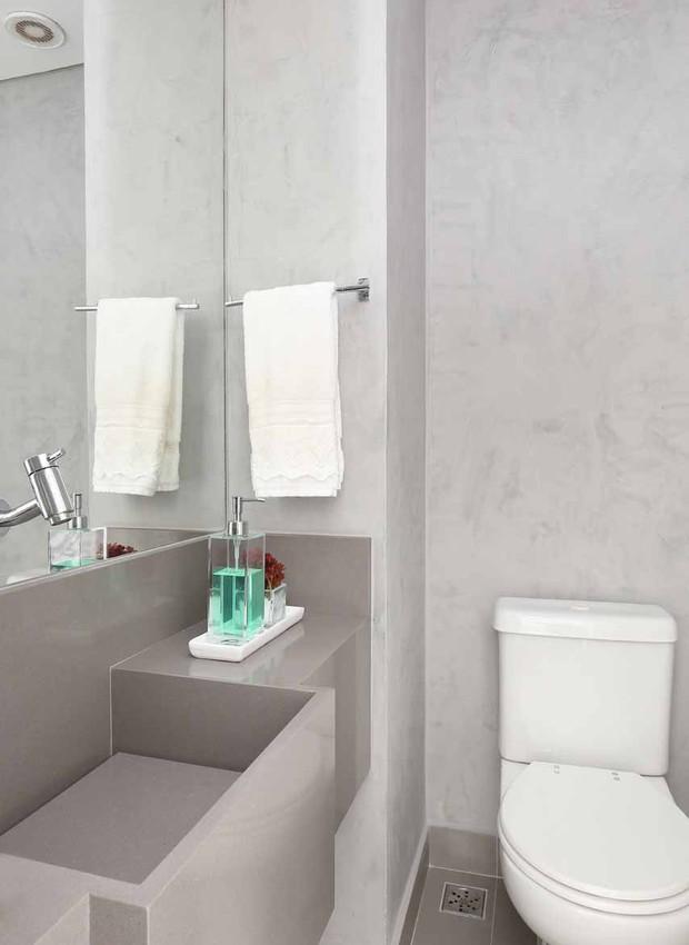 LAVABO | O destaque do ambiente é a cuba em Silestone Gris Expo da Marmoraria Thassos que harmoniza com as paredes em efeito mármore elefante da Suvinil. (Foto: Mariana Orsi/ Divulgação)