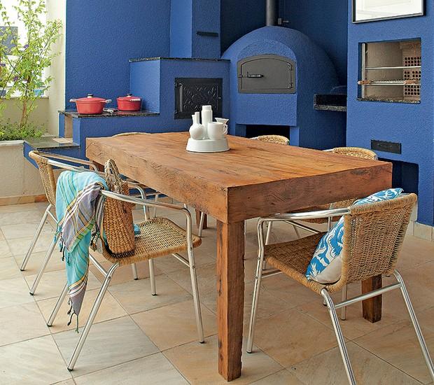 Com forno à lenha e churrasqueira, a varanda da cobertura ficou mais vibrante com o tom de azul intenso. A mesa é de madeira de demolição. Criação da arquiteta Andrea Murao (Foto: Victor Affaro/Editora Globo)