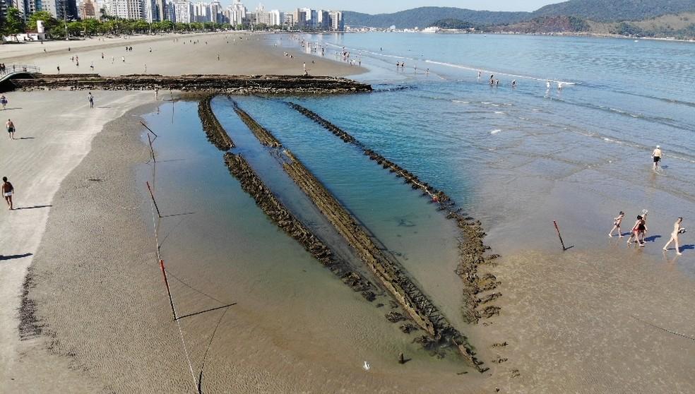 Banhistas caminham próximos à destroços de navio encalhado na orla de Santos, SP — Foto: Carlos Nogueira/A Tribuna Jornal