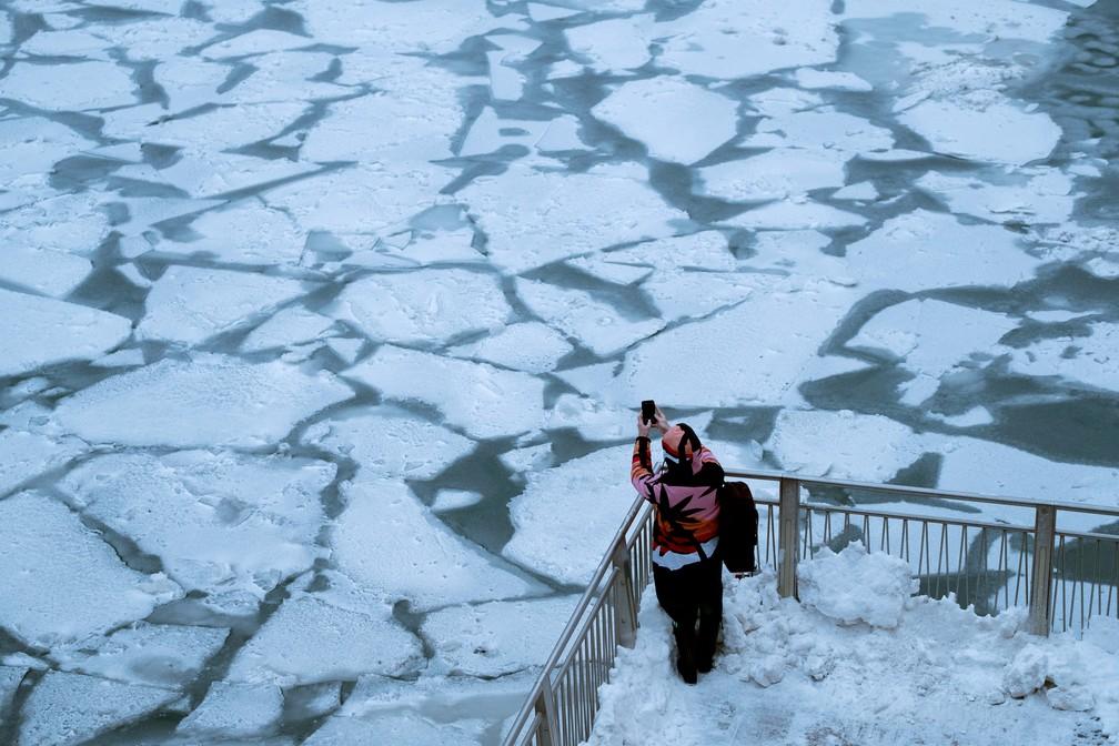 Pessoa observa rio gelado em Chicago — Foto: Pinar Istek/Reuters