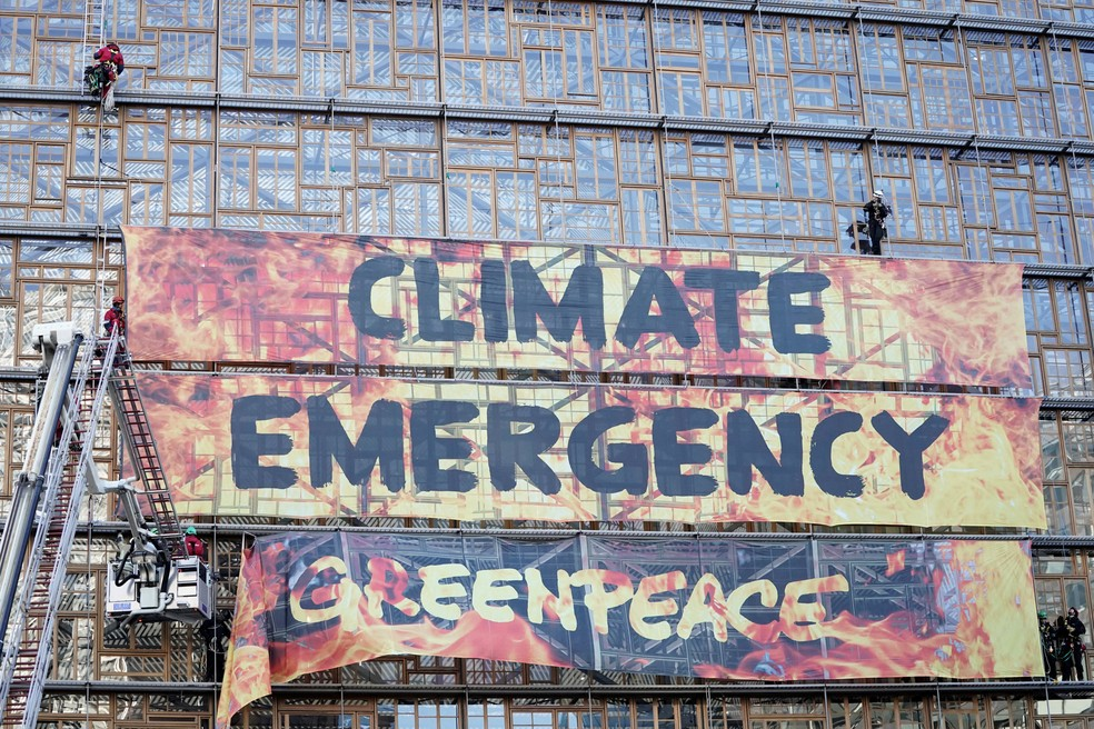12 de dezembro - Ativistas do Greenpeace são retirados por bombeiros após colocarem um cartaz em frente ao prédio do Conselho Europeu em protesto contra a emergência climática em Bruxelas, na Bélgica. Líderes da União Europeia se reuniram na quinta-feira (12) para tratar de onde virão os fundos na luta contra as mudanças climáticas — Foto: Kenzo Triboullard/AFP