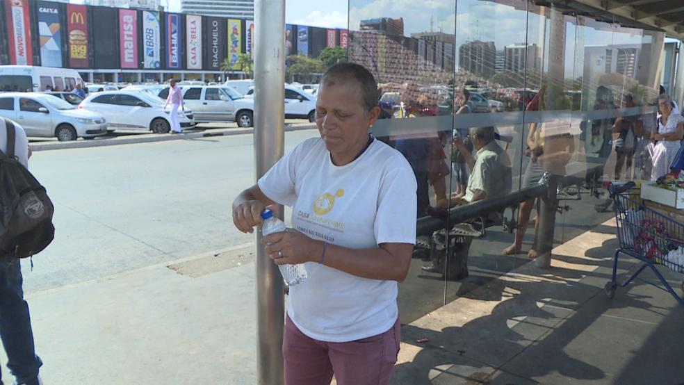 Maria Montalvão com garrafa de água; ela vende produto para custear exames de câncer no DF (Foto: TV Globo/Reprodução)
