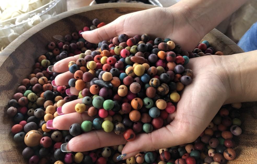 Artesã aplica as cores em sementes e fios de tucum. — Foto: Matheus Castro/G1