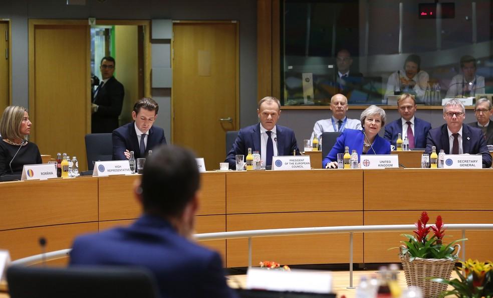 A primeira-ministra britânica, Theresa May, e o presidente do Conselho Europeu, Donald Tusk (centro),, participam de mesa redonda em uma cúpula da UE em Bruxelas, neste domingo (25) — Foto: Olivier Hoslet, Pool Photo via AP