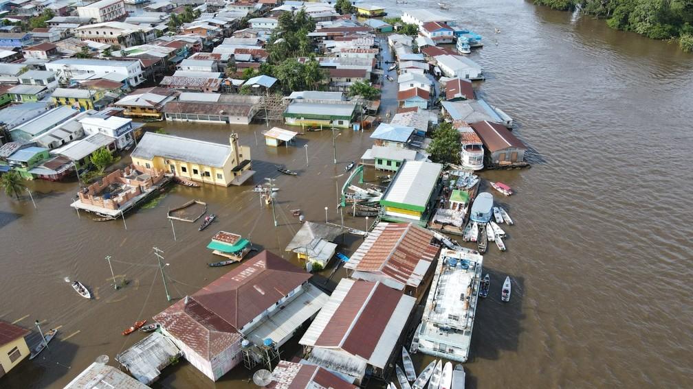 Cidade está 100% inundada pela cheia do Rio Solimões — Foto: Diego Peres/Secom e Arthur Castro/Secom