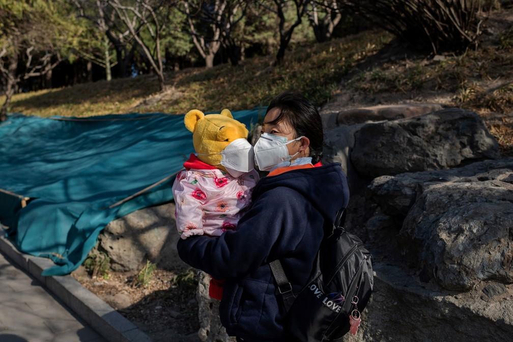 14 de março - Mulher com máscara de proteção contra o coronavírus segura urso também com máscara em parque em Pequim, na China, neste sábado (14)  — Foto: Nicolas Asfouri / AFP