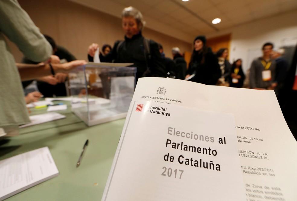 Um eleitor deposita sua cédula enquanto outros esperam para votar nas eleições regionais da Catalunha em uma mesa de voto em Sant Cugat del Valles. (Foto: Eric Gaillard/Reuters)