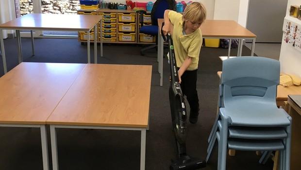 Sammy, de seis anos, disse que estava orgulhoso de poder usar um aspirador de pó, em vez de ter que fazer limpeza à mão (Foto: BBC News)