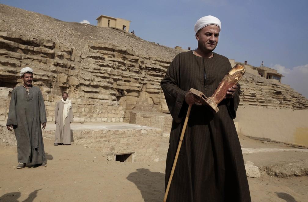 O líder da escavação segura uma estátua na tumba recém-descoberta em uma necrópole perto das pirâmides egípcias em Sacará, Giza, em 10 de novembro. O secretário egípcio de antiguidades diz que arqueologistas locaias encontraram sete tumbas da era faraônica contendo dúzias de múmias de gato e estátuas de madeira retratando outros animais. — Foto: Nariman El-Mofty/AP