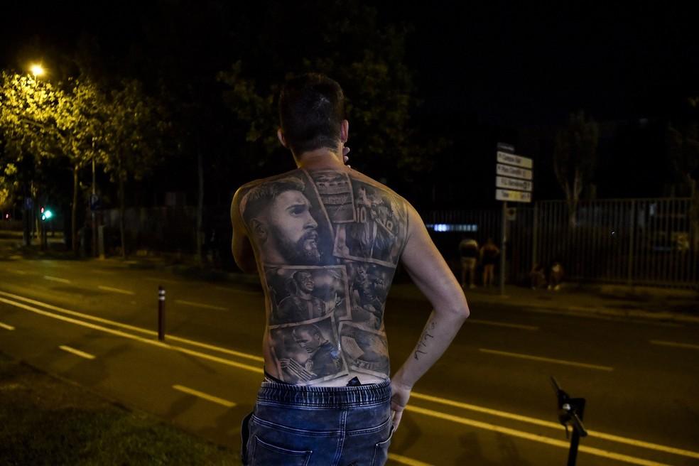 Torcedor exibe as tatuagens do ídolo Messi nos arredores do Camp Nou — Foto: PAU BARRENA / AFP