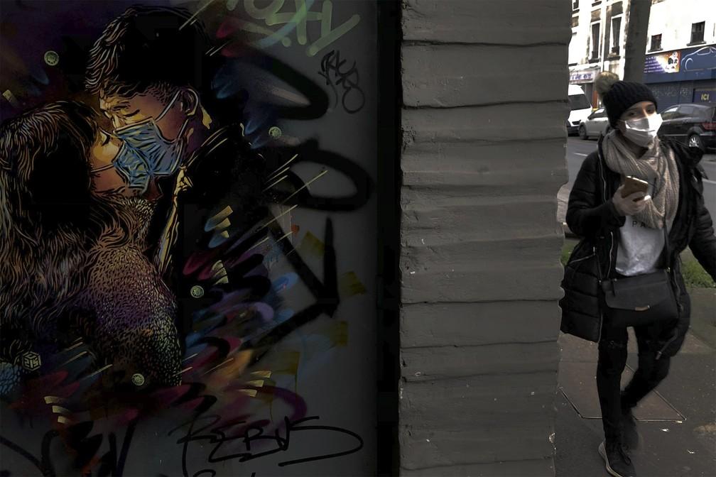 19 de março - Mulher passa de máscara ao lado de um grafite de um casal se beijando sem tirar as máscaras em tempo de coronavírus, obra do artista C215 que surgiu recentemente em um muro de Ivry-sur-Seine, perto de Paris, na França — Foto: Christophe Ena/AP