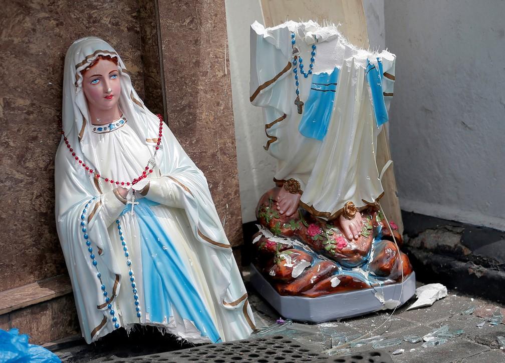 Estátua da Virgem Maria quebrada em duas partes é vista em frente ao Santuário de Santo Antônio, igreja de Kochchikade, após explosão em Colombo, — Foto: Dinuka Liyanawatte/Reuters