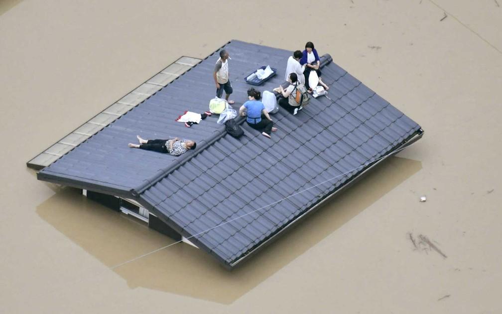 Vista aérea mostra moradores sobre telhado da casa submersa em uma área inundada em Kurashiki, sul do Japão (Foto: Kyodo / via Reuters)