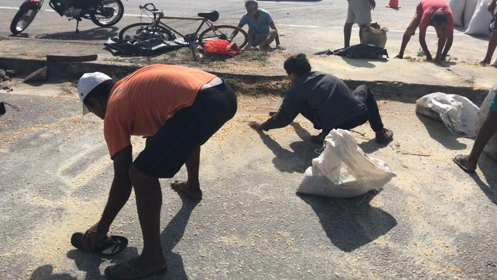 Moradores recolhem grãos de carreta tombada e levam em sacolas (Foto: Anézia Gomes/TVM)