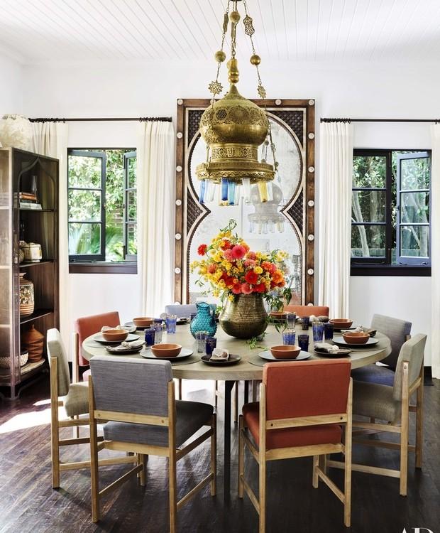A sala de jantar possui cadeiras coloridas, vasos rústicos e um lustre vintage (Foto: Douglas Friedman/ Reprodução)