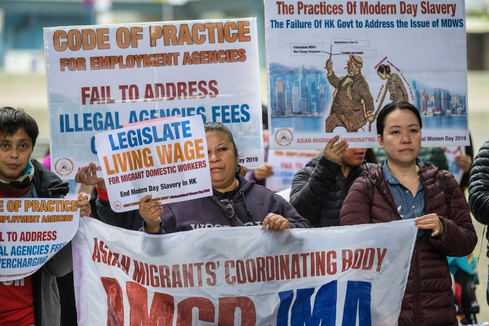 Trabalhadoras domésticos imigrantes e ativistas seguram cartazes durante protesto exigindo melhores condições de trabalho para marcar o Dia Internacional da Mulher, nesta sexta-feira (8), em Hong Kong  — Foto: Anthony Wallace / AFP