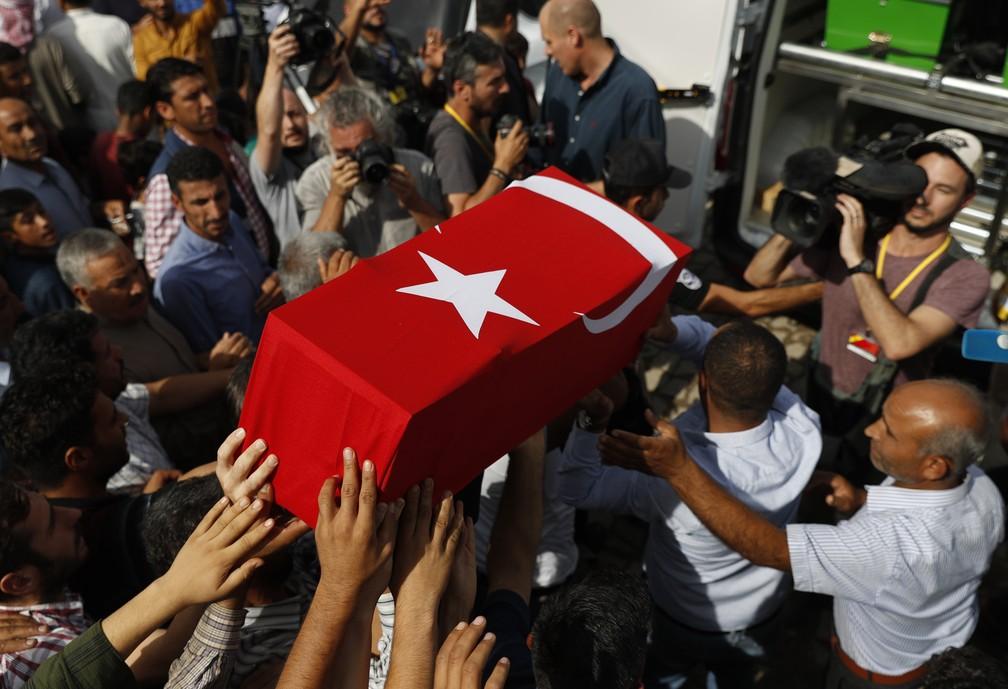 Multidão carrega corpo de bebê turco que morreu durante confronto na fronteira entre Turquia e Síria nesta sexta-feira (11) — Foto: Lefteris Pitarakis/AP Photo
