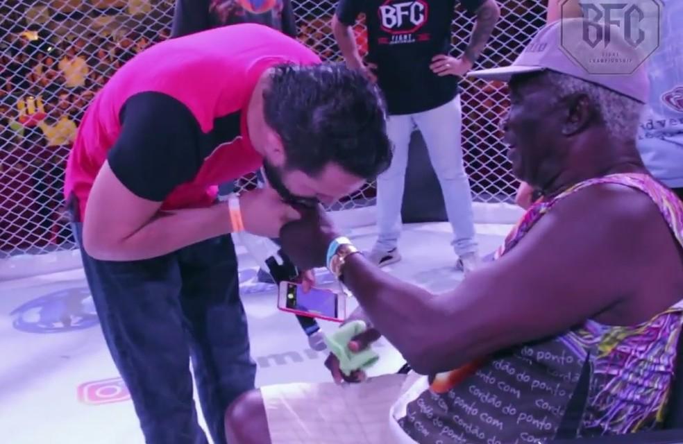Rony Jason pede bênção ao Rei Zulu no centro do cage do Bradar FC (Foto: reprodução/Youtube)