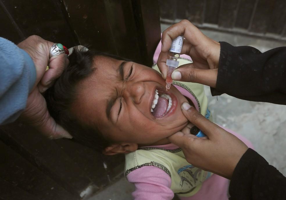 Um agente de saúde aplica a vacina contra poliomielite em uma criança em Lahore, no Paquistão — Foto: KM Chaudary/AP