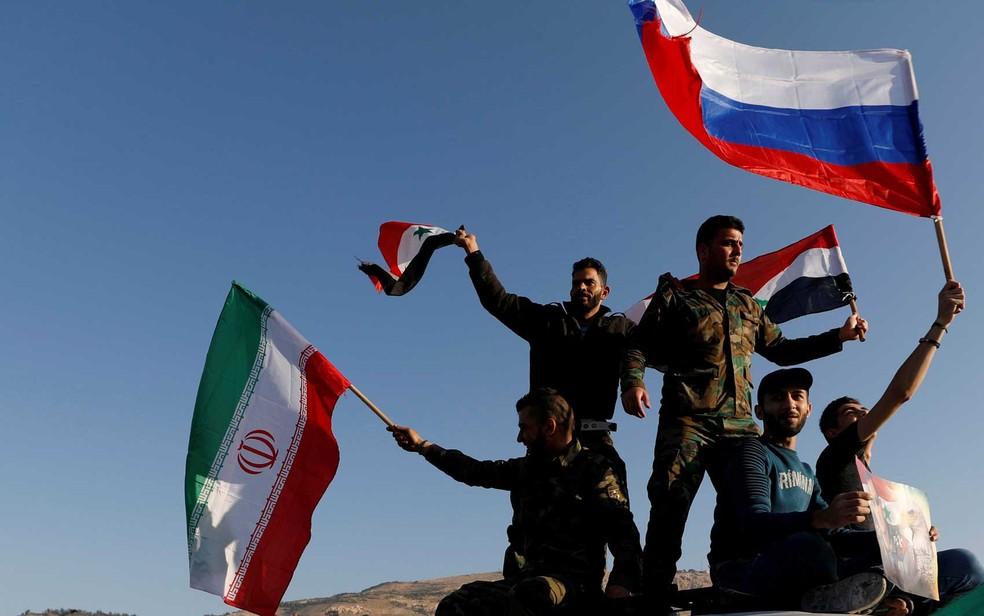 Sírios agitam bandeiras iranianas, russas e sírias durante protesto contra ataques aéreos liderados pelos EUA em Damasco (Foto: Omar Sanadiki / Reuters)