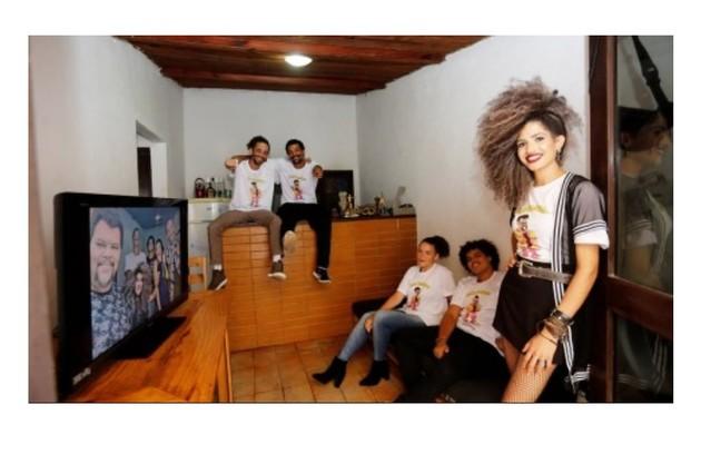 A família de Babu Santana na sala de sua casa. O ator aparece na TV. Ali ele faz lives para as redes sociais na quarentena (Foto: Editora Globo)