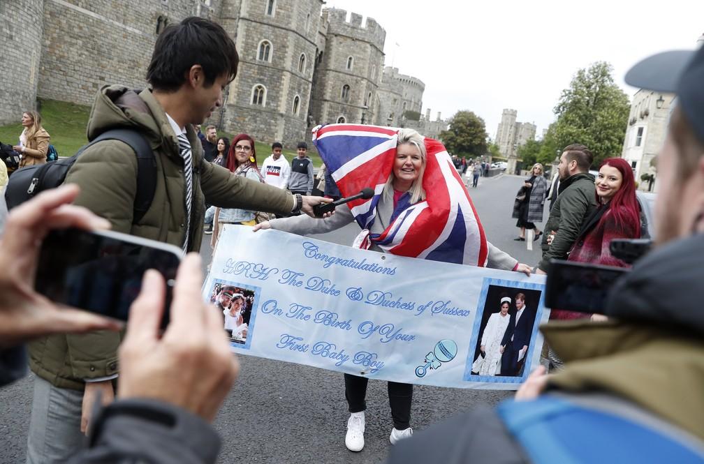 Fã carregando um cartaz parabenizando Meghan e Harry é entrevistada na segunda-feira (6), dia do nascimento do bebê. — Foto: Alastair Grant/AP