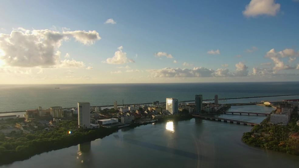 Recife é uma cidade no nível do mar e cortada por rios; na foto, vista da região central da capital, com mar ao fundo e rio em primeiro plano — Foto: Reprodução/TV Globo