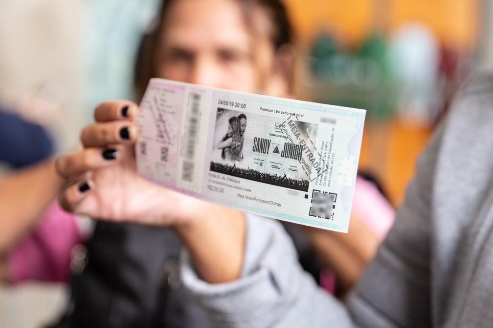 Gislaine Norberto, a primeira da fila, mostra um de seus 18 ingressos comprados para o show de Sandy e Junior em São Paulo, após sair da bilheteria do Pacaembu — Foto: Fábio Tito/G1
