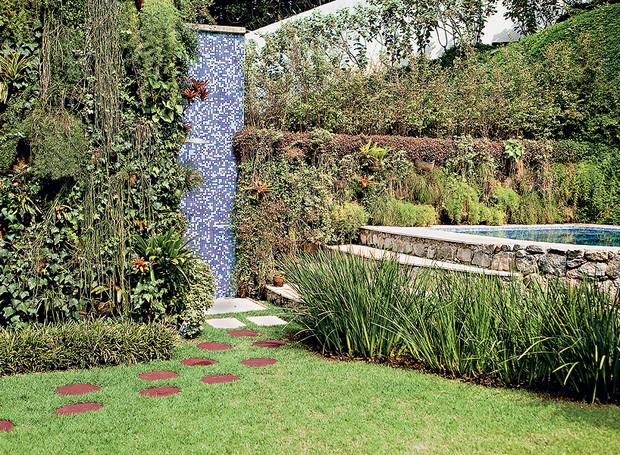 Em um terreno íngreme, o paisagista Sérgio Santana incluiu o spa com jeito de piscina natural. O cantinho de relaxamento foi parar ao lado do muro, por privacidade. O chuveirão, revestido de pastilhas azuis, fica discreto entre a vegetação (Foto: Edu Castello/Editora Globo)