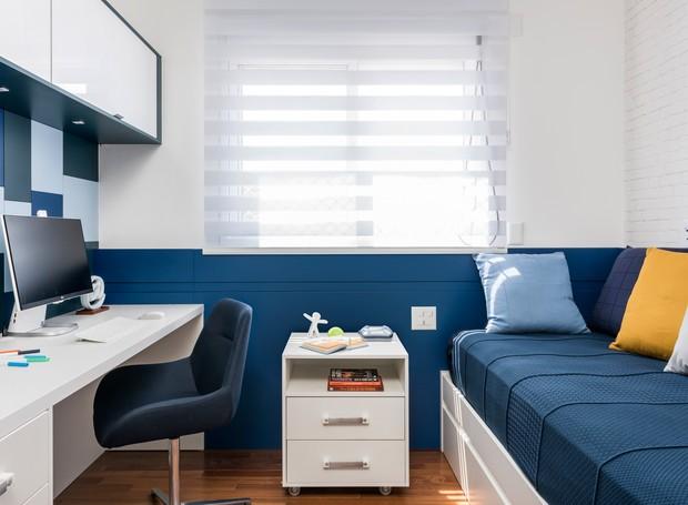 QUARTO | A escrivaninha feita sob medida, recebeu um painel de MDF com diferentes tons de azul. Dali, a estrutura segue em meia parede na superfície da janela, coberta pela persiana e da cama, que é revestida de tijolinhos. Nessa área, o painel imita uma  (Foto: Renato Navarro/ Divulgação)