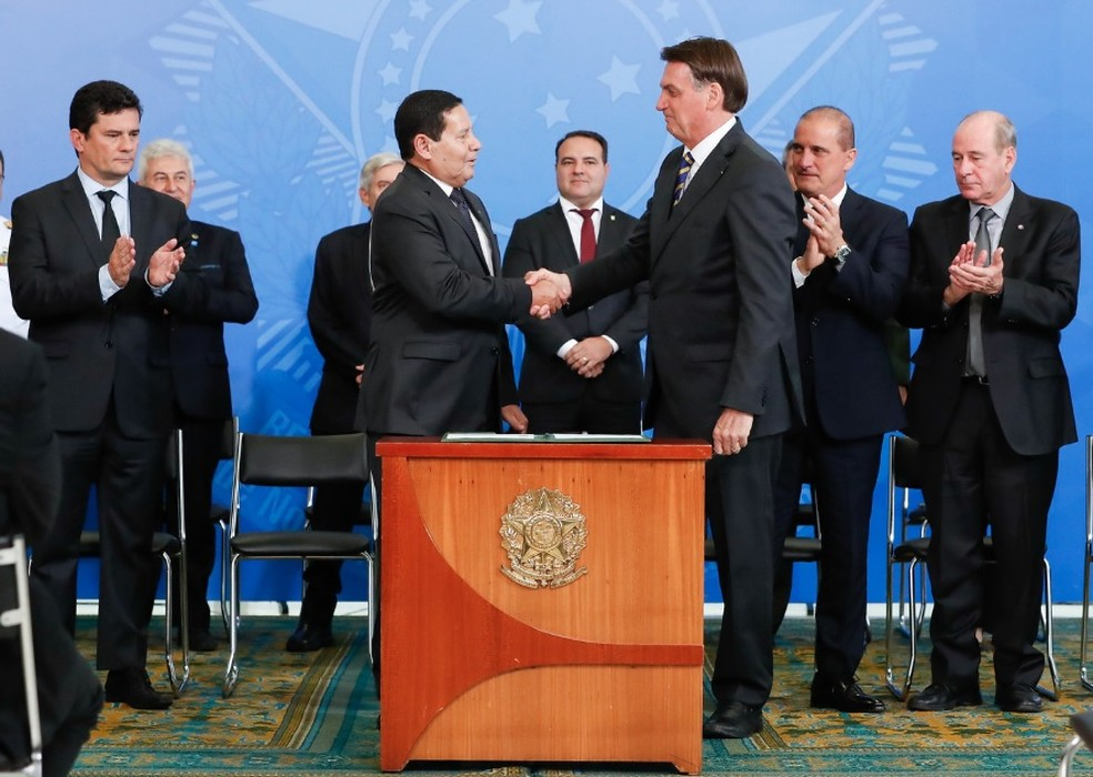 Presidente Jair Bolsonaro e vice-presidente Hamilton Mourão se cumprimentam após assinatura de decreto sobre Conselho da Amazônia Legal — Foto: Alan Santos/PR