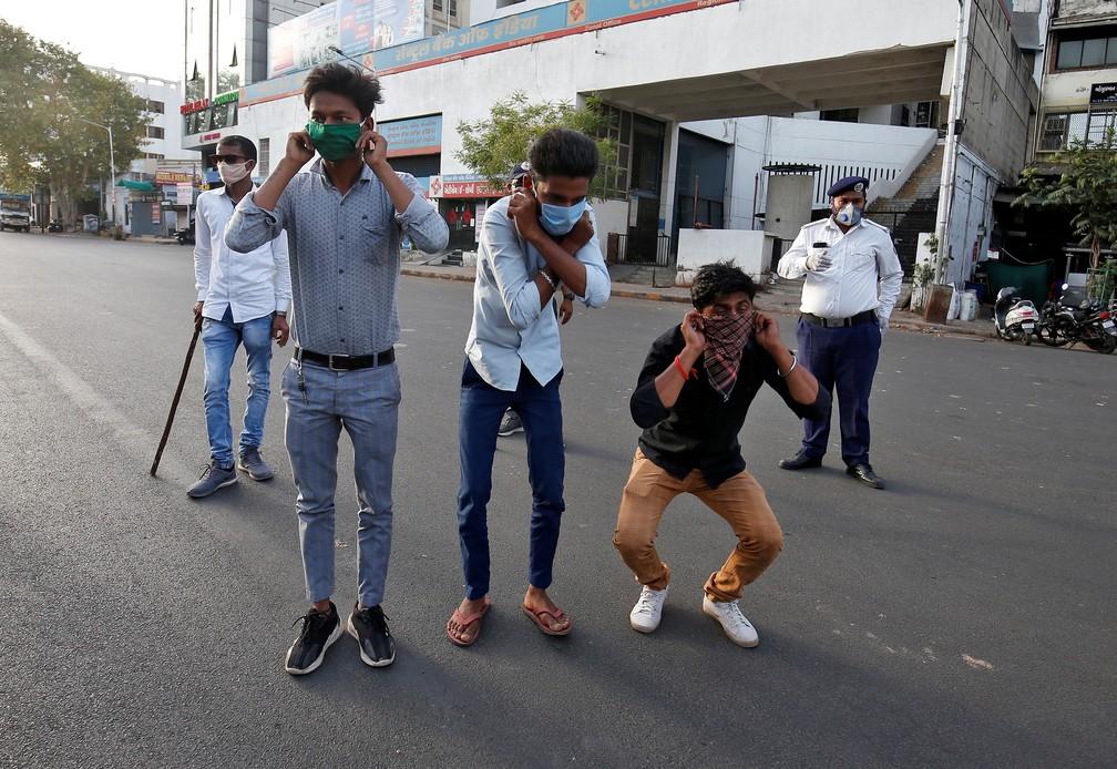 Indianos que não respeitaram isolamento são obrigados a fazer agachamentos com as mãos nas orelhas na ruas de Ahmedabad, na Índia, em 24 de março de 2020 — Foto: Amit Dave/Reuters