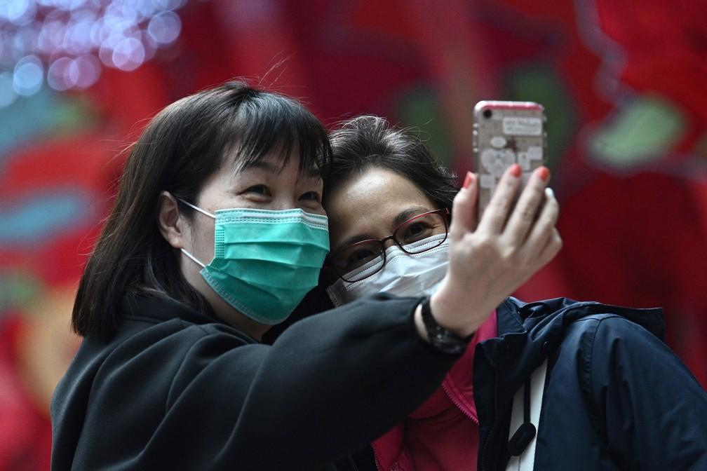 Mulheres com máscaras faciais tiram uma selfie em Hong Kong, nesta quarta-feira (5) — Foto: Anthony Wallace / AFP