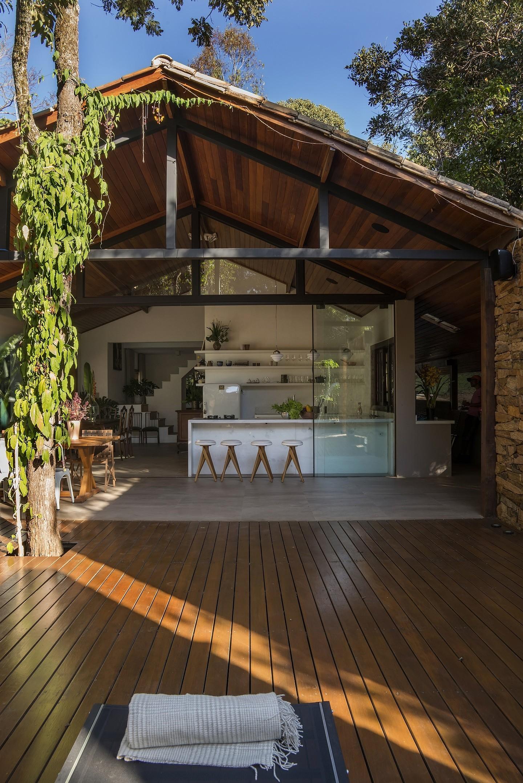 Area externa de casa com deck de madeira, árvore e vista para bar.