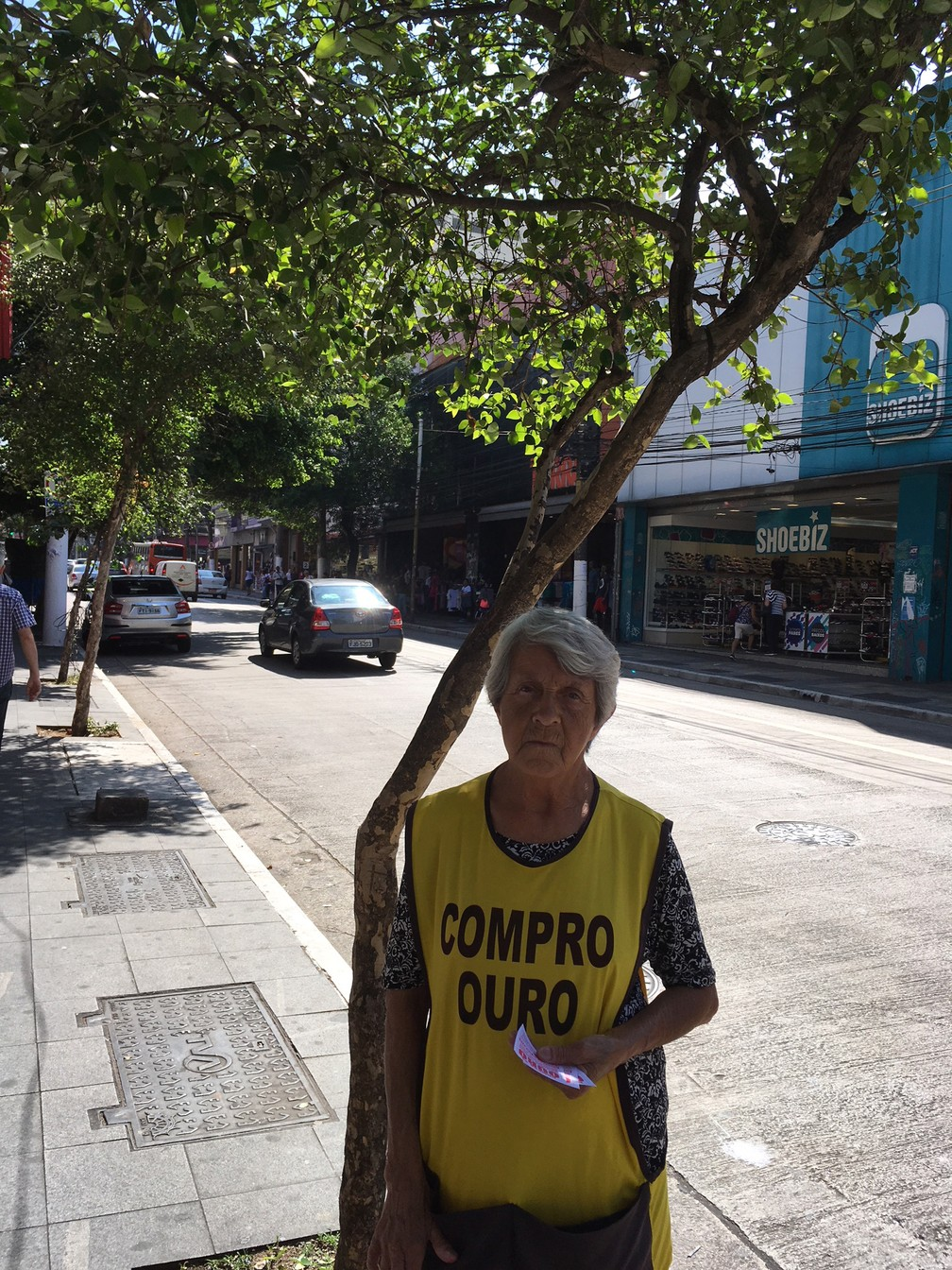 Iraci Ribeiro, de 74 anos, debaixo do pé de pitanga que faz sombra para seus dias de trabalho em pé, em jornada de 9 horas diárias — Foto: Marta Cavallini/G1