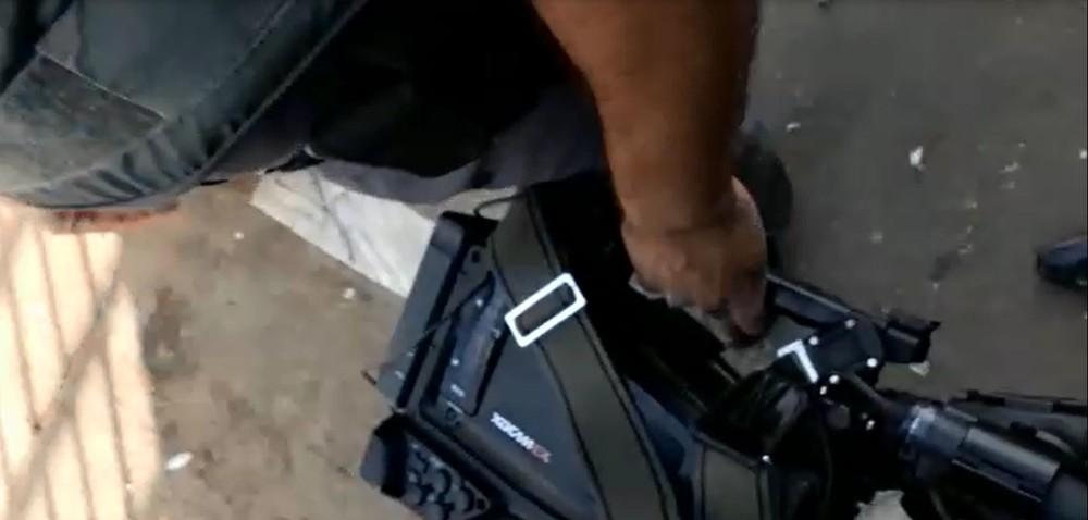 Policial segura a câmera do repórter cinematográfico do SBT (Foto: Reprodução/TV TEM)