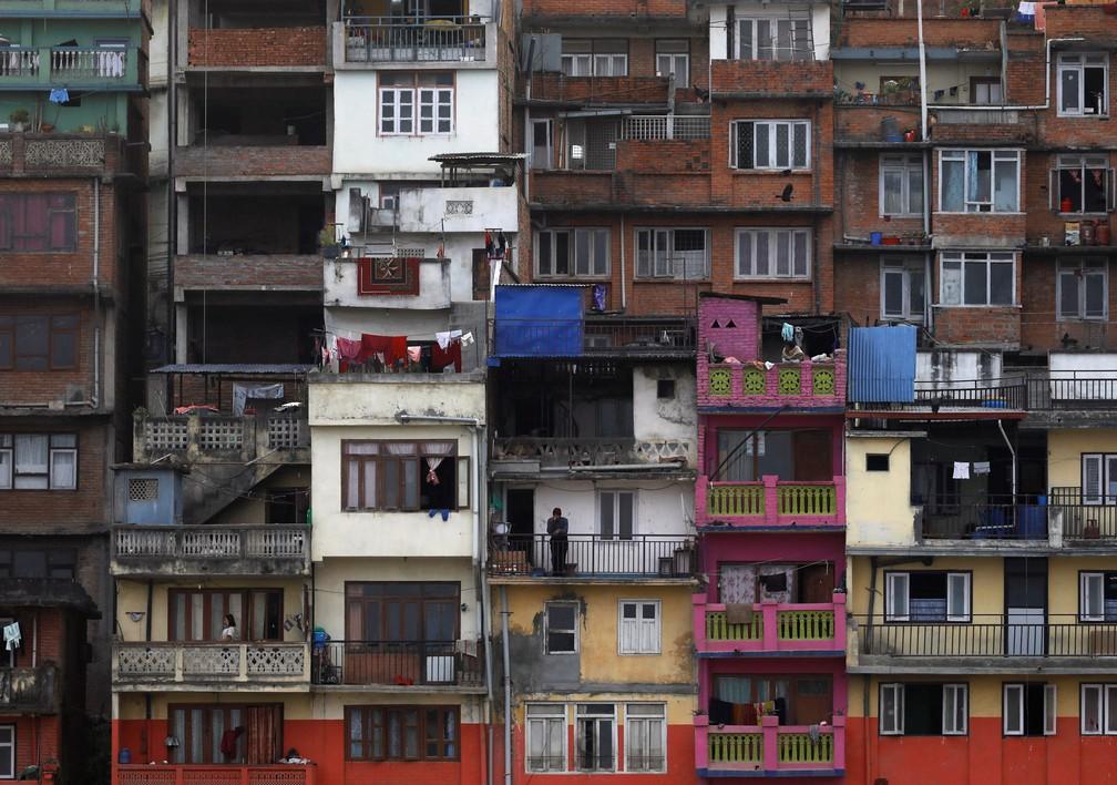 Um homem olha da varanda de sua casa enquanto bebe chá em  em Kathmandu, no Nepal, após o isolamento imposto pelo governo para evitar propagação do surto de doença por coronavírus (COVID-19) — Foto: Navesh Chitrakar/Reuters