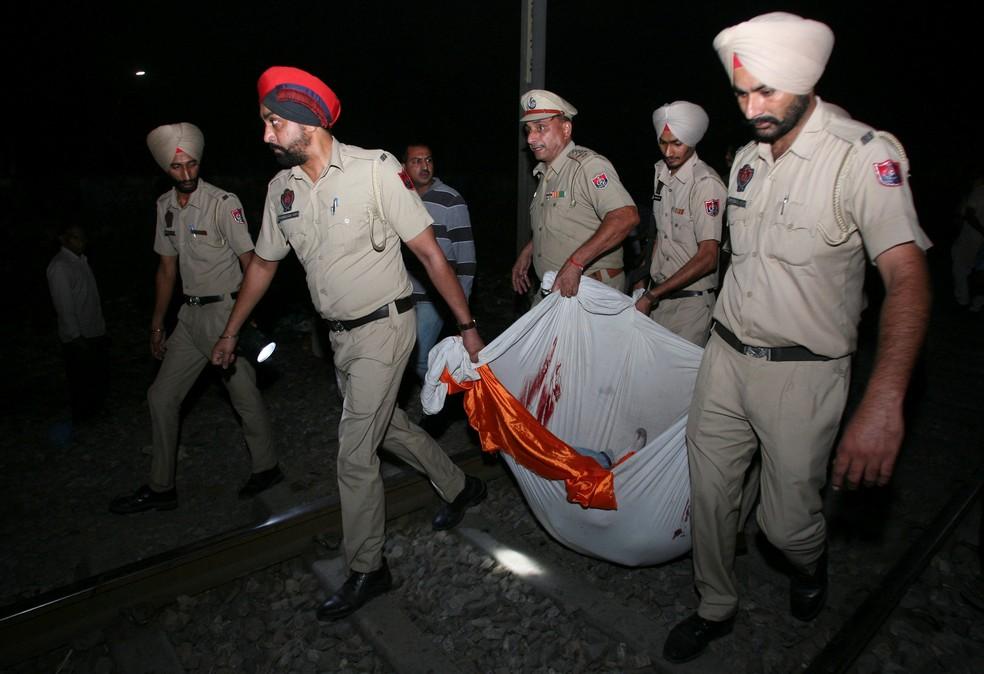Policiais carregam vítima de atropelamento de trem em Amritsar — Foto: Munish Sharma/Reuters