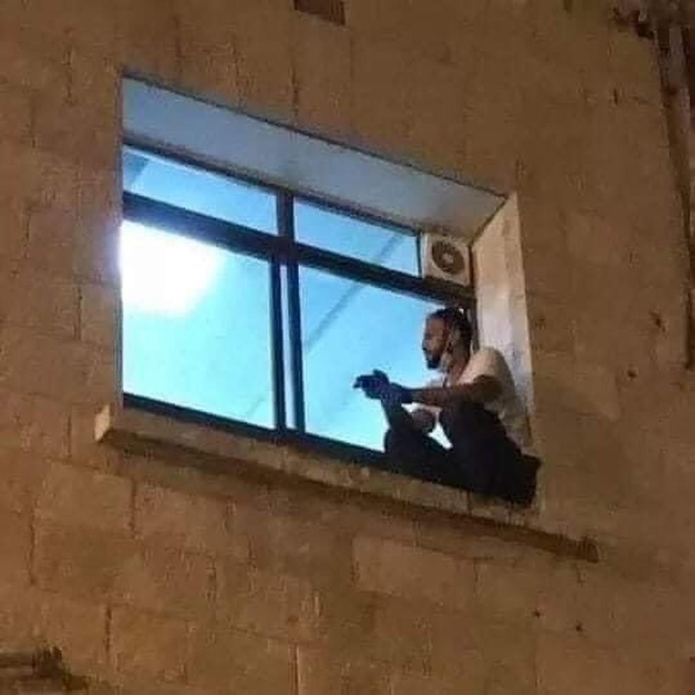 Jihad Al-Suwaiti após escalar até janela de hospital para ver sua mãe doente, internada com Covid-19, em julho — Foto: Reprodução/Twitter/Mohamad Safa