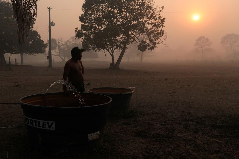 Um homem que trabalha em uma fazenda observa a fumaça das queimadas subindo pelo ar em Poconé (MT), no Pantanal — Foto: Amanda Perobelli/Reuters